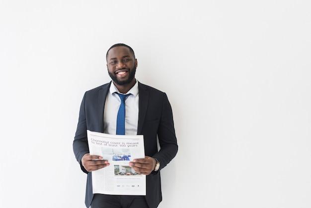Biznesmen trzyma gazetę i ono uśmiecha się