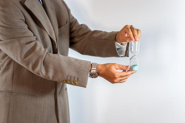 Biznesmen trzyma hourglass odizolowywający na bielu