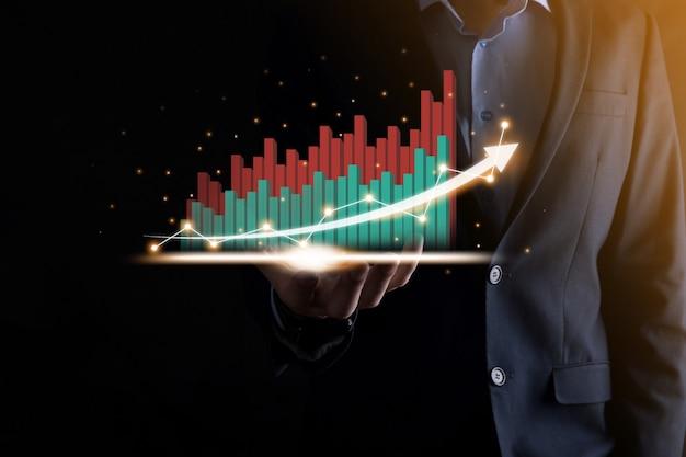 Biznesmen trzyma i pokazuje rosnący wirtualny hologram statystyk