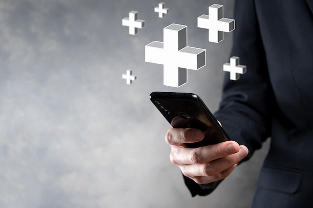 Biznesmen trzyma ikonę 3d plus, człowiek trzyma w ręku, oferując pozytywne rzeczy, takie jak zysk, korzyści, rozwój, csr reprezentowane przez znak plus