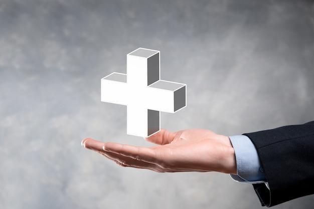 Biznesmen trzyma ikonę 3d plus, człowiek trzyma w ręku oferuje pozytywne rzeczy, takie jak zysk, korzyści, rozwój, csr reprezentowane przez znak plus. ręka pokazuje znak plus.