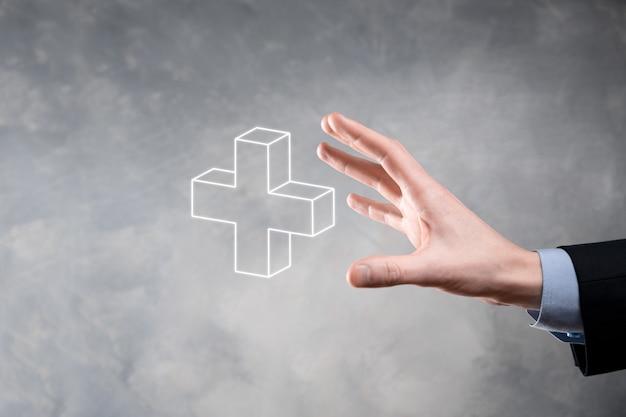 Biznesmen trzyma ikonę 3d plus, człowiek trzymać w ręku oferuje pozytywne rzeczy, takie jak zysk, korzyści