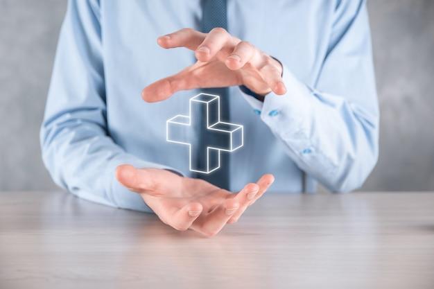 Biznesmen trzyma ikonę 3d plus, człowiek trzymać w ręku oferuje pozytywne rzeczy, takie jak zysk
