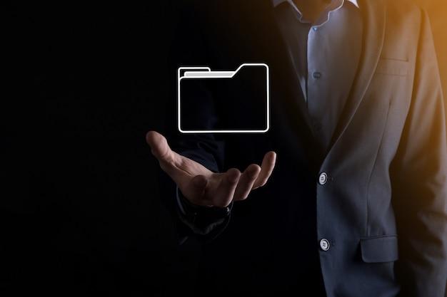 Biznesmen trzyma ikonę folderu. system zarządzania dokumentami lub konfiguracja dms przez konsultanta it przy użyciu nowoczesnego komputera przeszukuje zarządzanie informacjami i plikami korporacyjnymi. przetwarzanie biznesowe.
