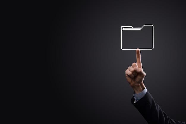 Biznesmen trzyma ikonę folderu. system zarządzania dokumentami lub konfiguracja dms przez konsultanta it z nowoczesnym komputerem przeszukuje zarządzanie informacjami i plikami korporacyjnymi.
