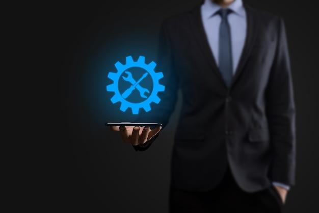 Biznesmen trzyma ikonę koła zębatego z narzędziami. gearing. concept cyfrowego diagramu ostrości celu, interfejsów wykresu, wirtualnego ekranu interfejsu użytkownika, sieci połączeń.