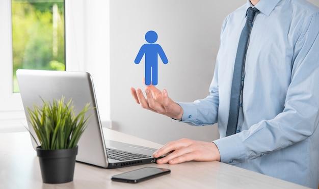 Biznesmen trzyma ikonę osoby człowieka na ciemnym tle. hr człowieka, ludzie icontechnology process