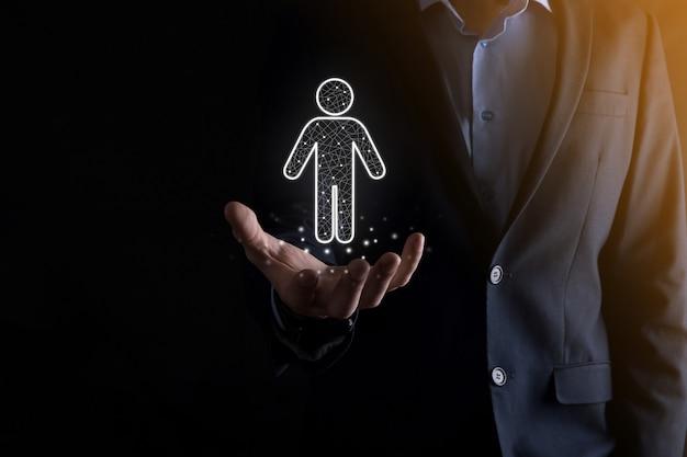 Biznesmen trzyma ikonę osoby człowieka na ścianie ciemnego tonu. hr człowiek, ikona ludzi proces technologiczny system biznesowy z rekrutacją, zatrudnianiem, budowaniem zespołu. koncepcja struktury organizacyjnej.