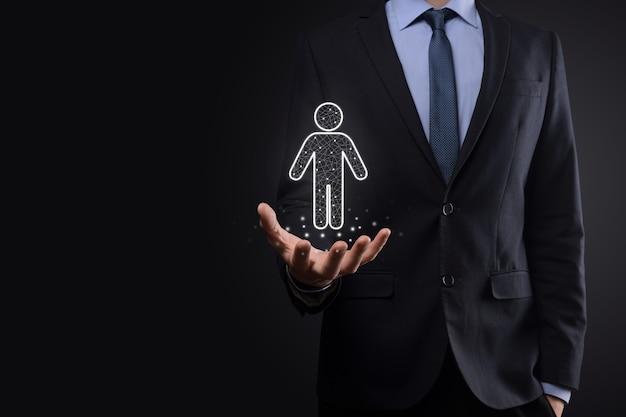 Biznesmen trzyma ikonę osoby człowieka na tle ciemnego tonu. hr człowiek, ikona ludzi proces technologiczny system biznesowy z rekrutacją, zatrudnianiem, budowaniem zespołu. koncepcja struktury organizacyjnej