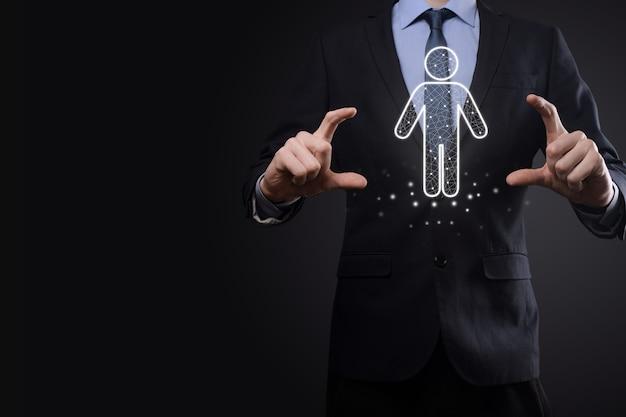 Biznesmen trzyma ikonę osoby człowieka na tle ciemnego tonu. hr człowiek, ikona ludzi proces technologiczny system biznesowy z rekrutacją, zatrudnianiem, budowaniem zespołu. koncepcja struktury organizacyjnej.