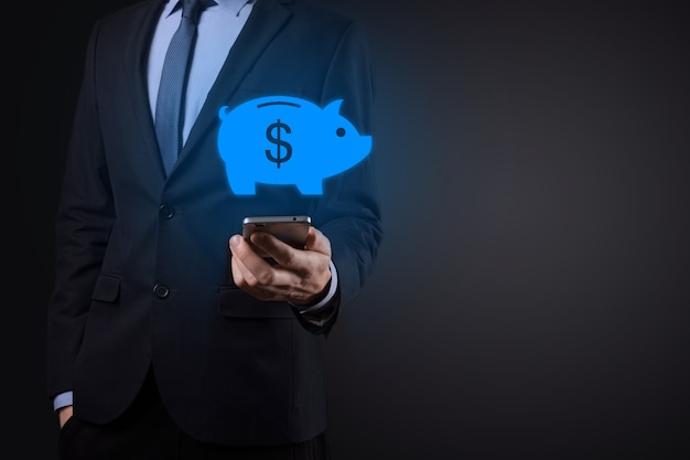 Biznesmen trzyma ikonę skarbonki. planowanie wydatków biznesowych i pieniędzy i budżet inwestycyjny, koncepcja oszczędzania pieniędzy biznesowych. zapisanie lub inwestycja.