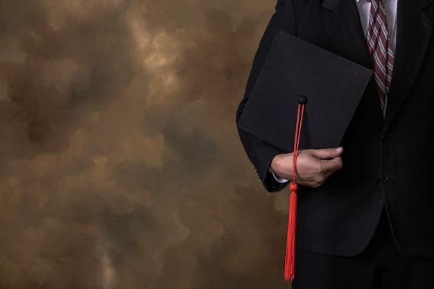 Biznesmen trzyma kapelusz ukończenia szkoły