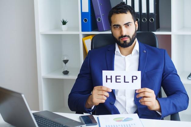 Biznesmen trzyma kartę z tekst pomocą