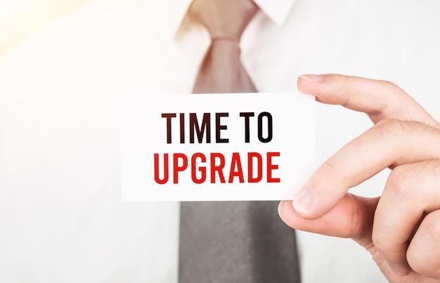 Biznesmen trzyma kartę z tekstem czas na uaktualnienie, koncepcja biznesowa
