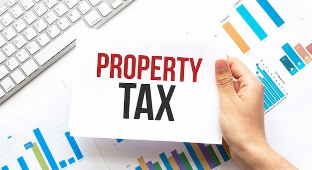 Biznesmen trzyma kartę z tekstem podatek od nieruchomości. klawiatura, schemat
