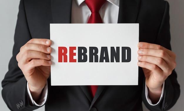 Biznesmen trzyma kartę z tekstem rebrand