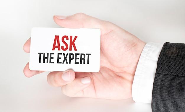 Biznesmen trzyma kartę z tekstem zapytaj eksperta