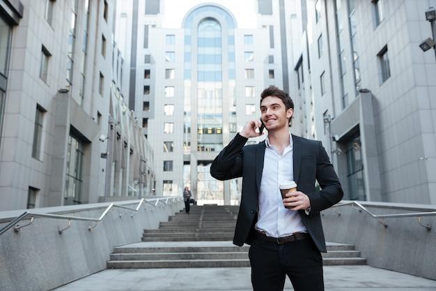 Biznesmen trzyma kawę i telefon