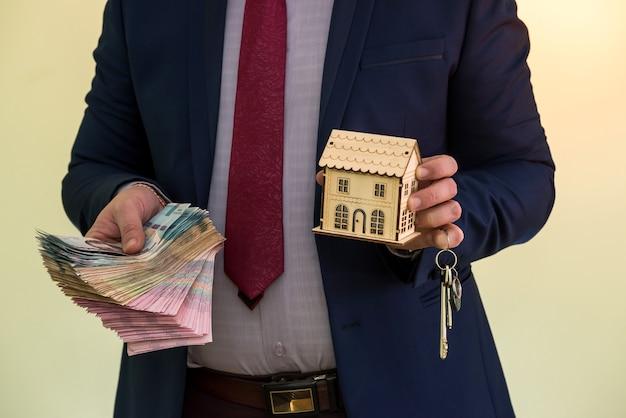 Biznesmen trzyma klucze do mieszkania za czyjeś pieniądze po sprzedaży lub wynajmie domu. zawarcie udanej umowy
