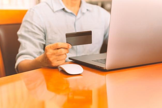 Biznesmen trzyma kredytową kartę i pracuje na laptopie.