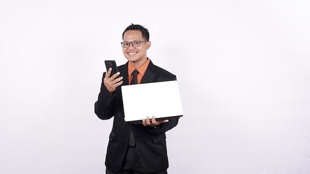 Biznesmen trzyma laptopa i patrzy na telefon komórkowy na białym tle