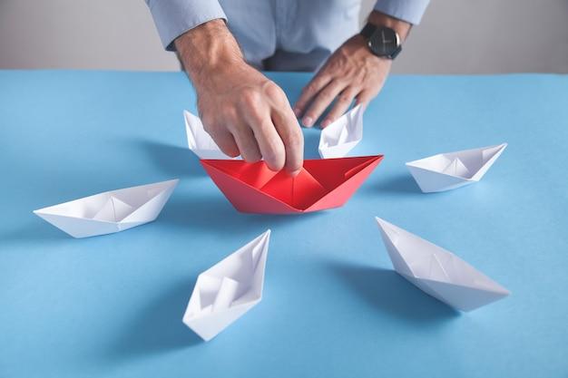 Biznesmen trzyma łódź papieru czerwony origami. białe łodzie. biznes, przywództwo