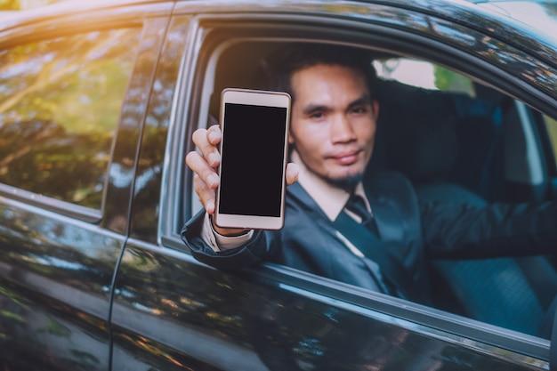Biznesmen trzyma mądrze telefon i obsiadanie w samochodzie