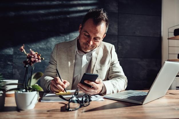 Biznesmen trzyma mądrze telefon i pisze na adhezyjnych notatkach