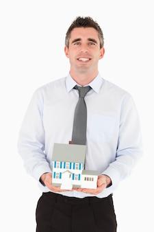 Biznesmen trzyma miniaturowego dom