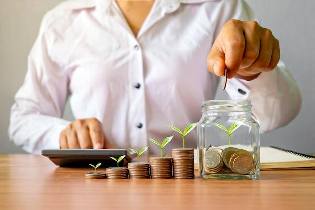 Biznesmen trzyma monety w słoiku z pieniędzmi, a na ułożonych monetach rośnie drzewo. koncepcja rozwoju biznesu, finanse, inwestycje