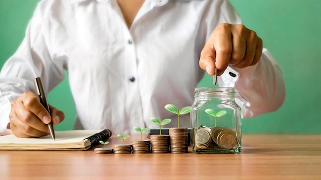 Biznesmen trzyma monety w słoiku z pieniędzmi, a na ułożonych monetach rośnie drzewo