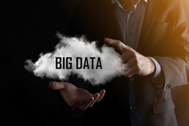 Biznesmen trzyma napis big data. kłódka, mózg, człowiek, planeta, wykres, lupa, koła zębate, chmura, siatka, dokument, list, ikona telefonu.