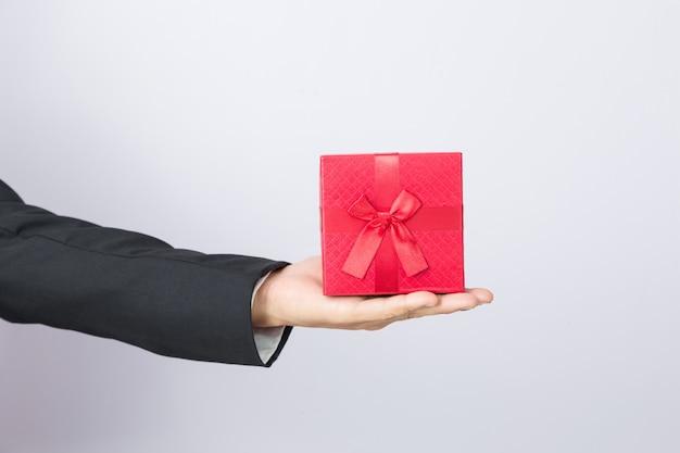 Biznesmen trzyma out prezent czerwieni pudełko, odosobniony tło