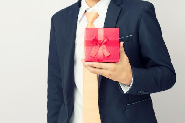 Biznesmen trzyma out prezenta czerwonego pudełko, odosobniony tło