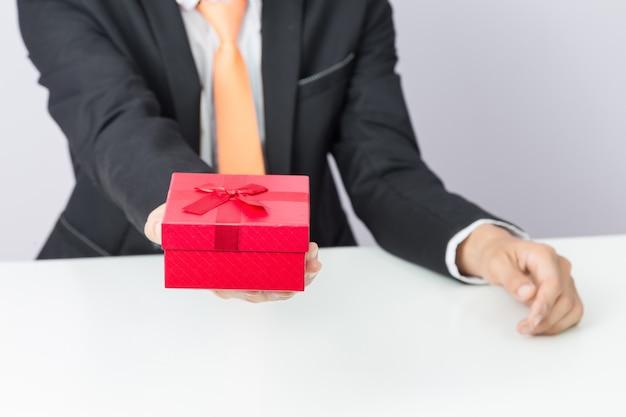 Biznesmen trzyma out prezenta czerwonego pudełko