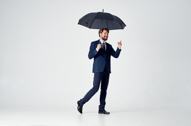 Biznesmen trzyma parasol elegancki styl pewność siebie pogoda
