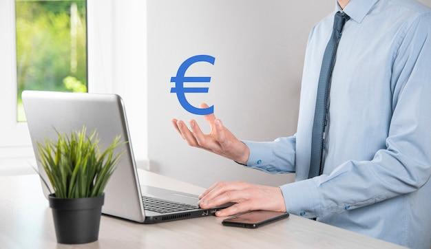 Biznesmen trzyma pieniądze monety ikony eur lub euro na ciemnym tle tonu... rosnąca koncepcja pieniędzy na inwestycje biznesowe i finanse