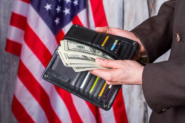 Biznesmen trzyma portfel z dolarami. amerykańska flaga, portfel i pieniądze. pensja przyszła w samą porę. praca, bogactwo i patriotyzm.