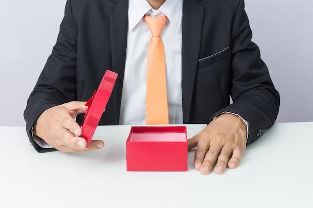 Biznesmen trzyma pudełko czerwony prezent