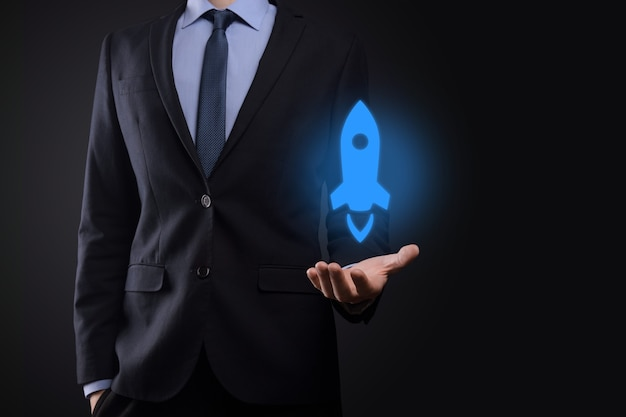 Biznesmen trzyma rakietę tabletu i ikony jest uruchamiany i szybuje wylatuje z ekranu