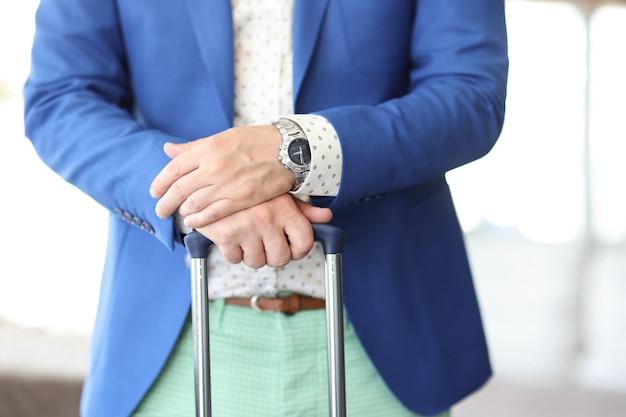 Biznesmen trzyma ręce na rączce walizki
