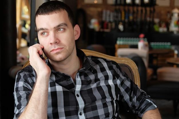 Biznesmen trzyma smartfona i siedzi w kawiarni.