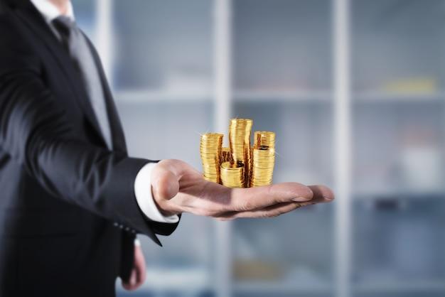 Biznesmen trzyma stosy złotych pieniędzy