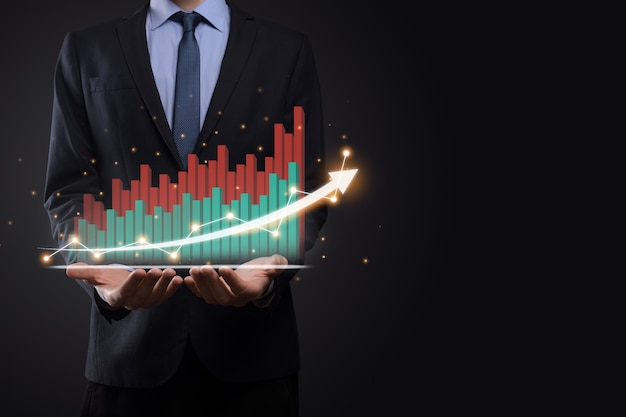 Biznesmen trzyma tablet i pokazuje rosnący wirtualny hologram statystyk, wykresu i wykresu ze strzałką w górę na ciemnym tle. giełda papierów wartościowych. koncepcja rozwoju, planowania i strategii biznesowej.