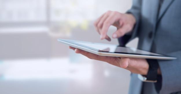 Biznesmen trzyma tablet w jasnym biurze