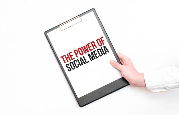 Biznesmen trzyma teczkę z kartką papieru z napisem potęga social media. pomysł na biznes.