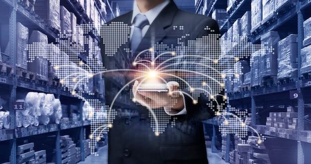 Biznesmen trzyma telefon komórkowy, aby planować, sprawdzać, kontrolować zapasy towarów w magazynie. biznesmen używa inteligentnego telefonu zarządza magazynem przez internet pokaż mapę świata, logistykę, ładunek, dystrybucję koncepcji