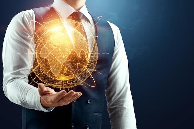 Biznesmen trzyma w dłoni hologram kuli ziemskiej
