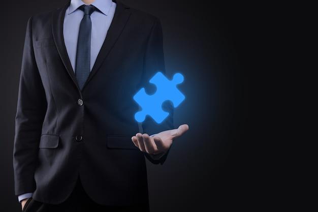 Biznesmen trzyma w rękach kawałek układanki. koncepcja współpracy, pracy zespołowej, pomocy i wsparcia w biznesie.