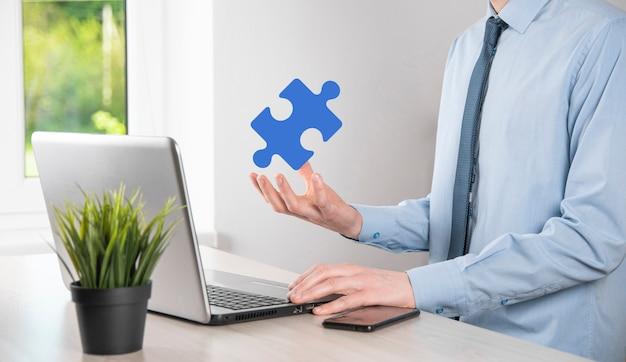 Biznesmen trzyma w rękach kawałek układanki. pojęcie współpracy, pracy zespołowej, pomocy i wsparcia w biznesie.